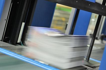 Druckexemplare verlassen eine Umreifungsanlage